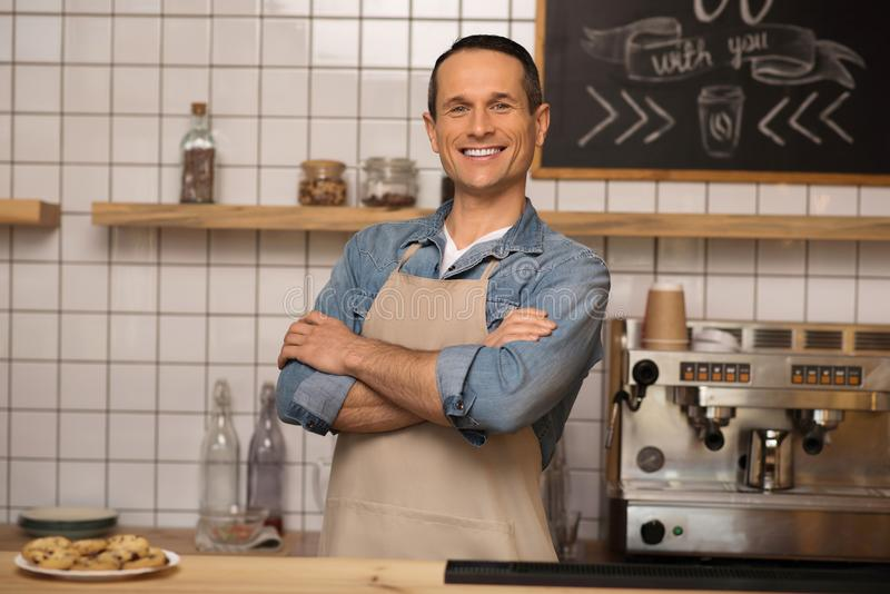 Barista in apron with crossed arms. Portrait of smiling barista in apron with crossed arms standing in coffee shop and looking at camera royalty free stock photo