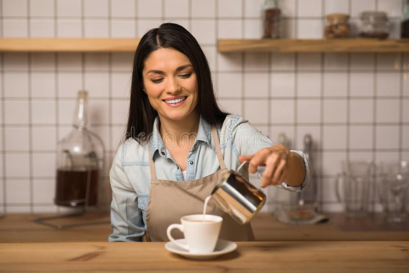 Barista pouring milk into coffee. Portrait of smiling barista pouring milk into coffee stock image