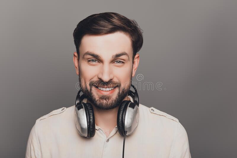 Portrait of smiling bearded handsome music lover with headphones royalty free stock images