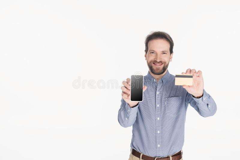 portrait of smiling bearded man showing smartphone with blank screen and credit card in hands royalty free stock image