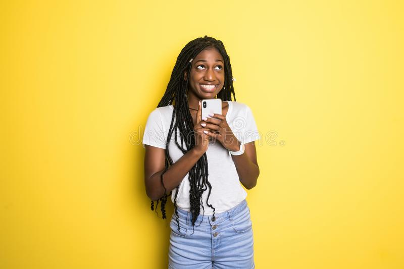 Portrait of a smiling beautiful african woman with afro hairstyle, holding mobile phone standing over yellow background royalty free stock photography