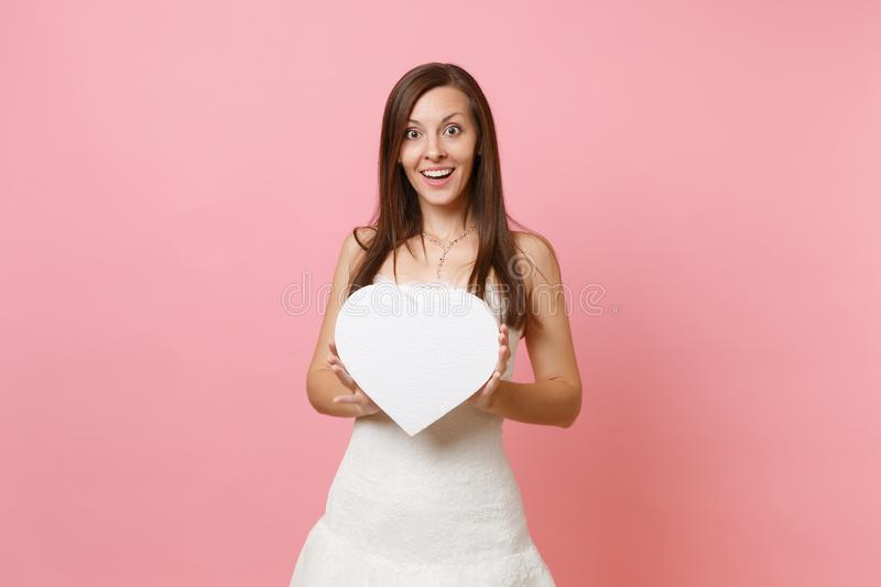Portrait of smiling beautiful bride woman in elegant white wedding dress standing holding white heart with copy space stock photos