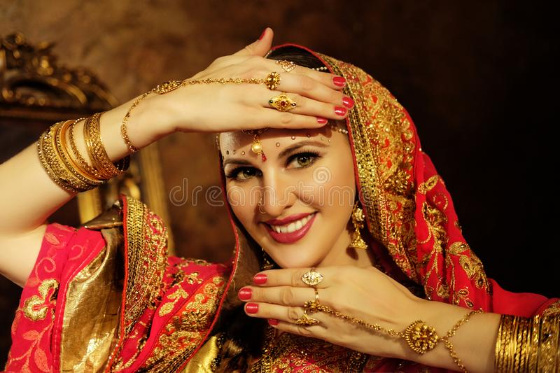 Portrait smiling of beautiful indian girl at home. Young woman model with golden jewelry set . Traditional Indian costume royalty free stock photos