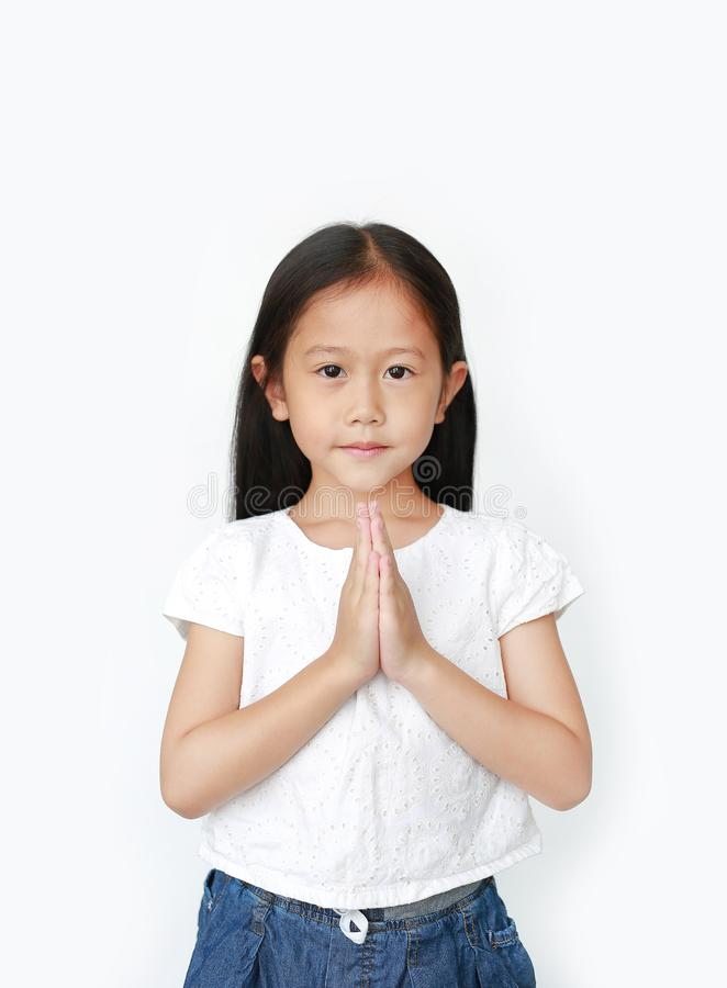 Portrait smiling beautiful little asian girl praying isolated over white background. Sawasdee is meaning hello stock photos