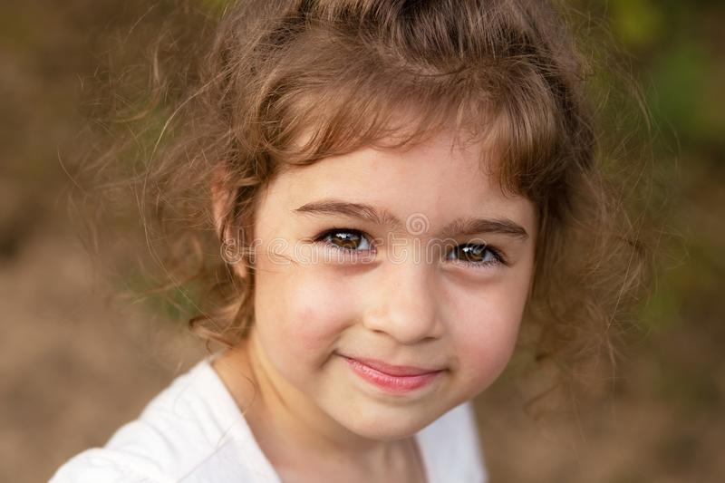 Portrait of smiling beautiful little girl at summer park. Cute child looking at the camera royalty free stock images