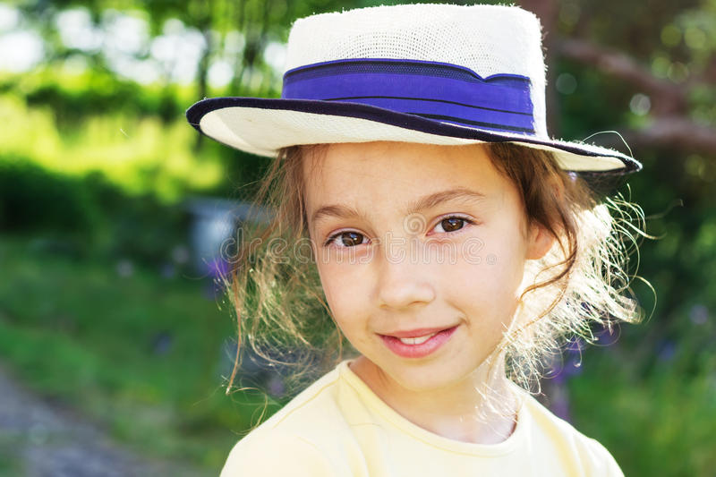 Portrait of smiling beautiful teenage in hat, against green of summer park. royalty free stock photo
