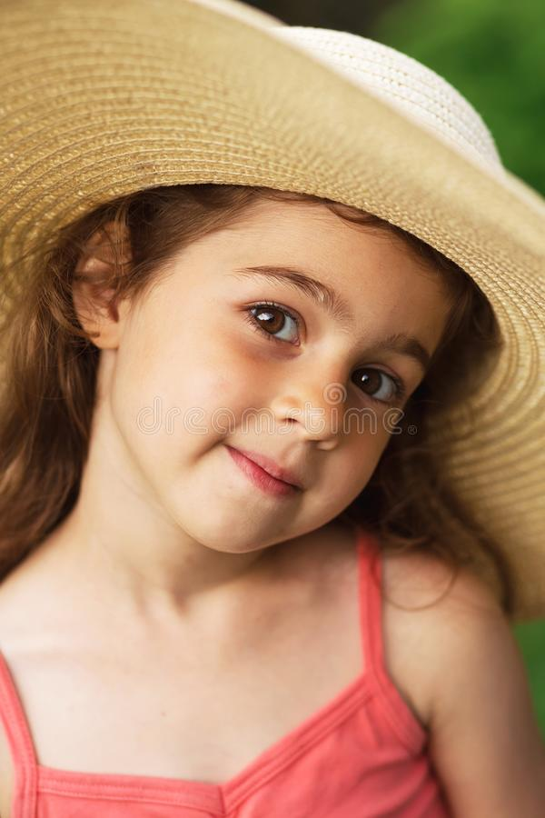 Portrait of smiling beautiful toddler in wide-brimmed hat at green of summer park. Portrait of smiling Cute toddler in wide-brimmed hat at green of summer park stock photos