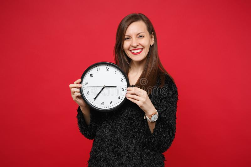 Portrait of smiling beautiful young woman in black fur sweater holding round clock isolated on bright red wall stock images