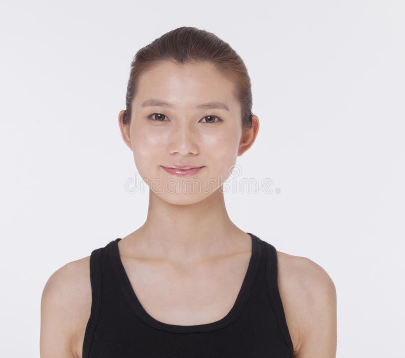 Portrait of smiling beautiful young woman in a black tank top, studio shot royalty free stock photography