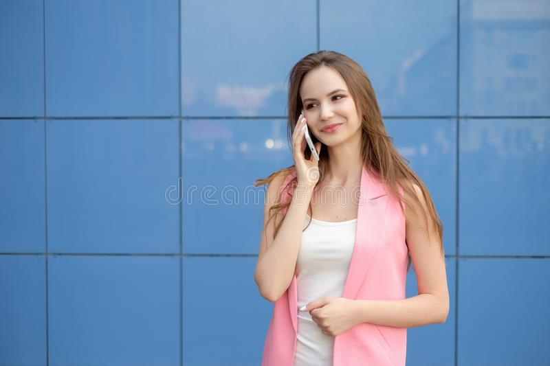 Portrait of smiling beautiful young woman close up with mobile phone outdoor stock image