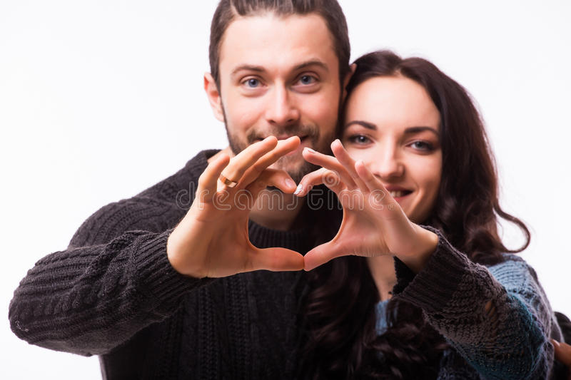 Portrait of smiling beauty girl and her handsome boyfriend making shape of heart by their hands. stock photos