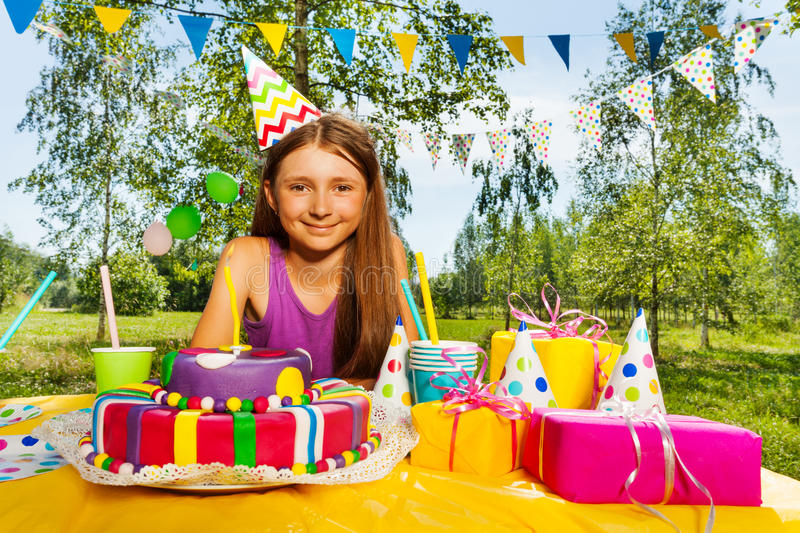 Portrait of smiling birthday girl in party hat. Sitting at the festive table outdoor in summer royalty free stock image
