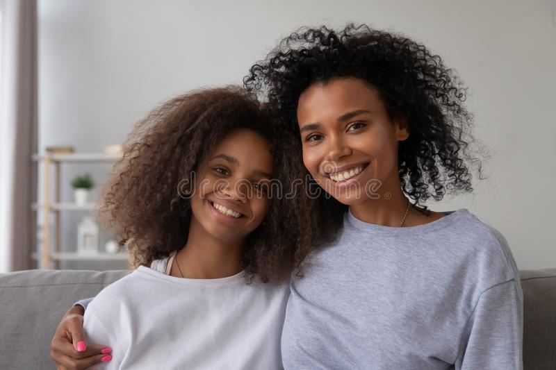 Portrait of smiling black mom and daughter hugging on couch. Portrait of happy African American mother and daughter hug sitting on couch at home, smiling black royalty free stock image