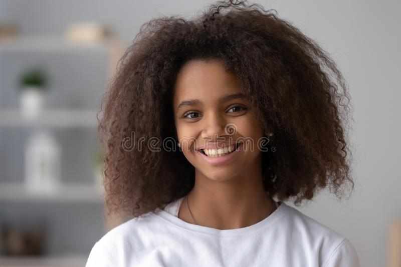 Portrait of smiling black teenage girl posing at home stock photography