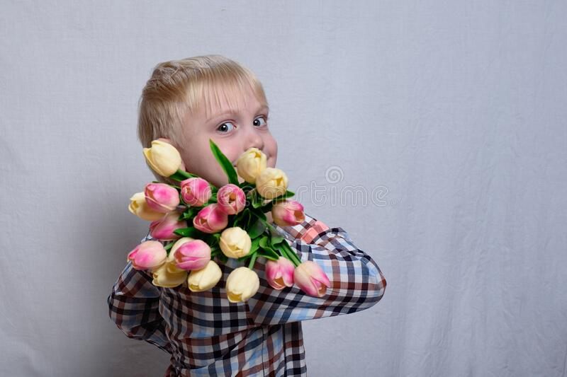 Portrait smiling blond boy with a bouquet of tulips. White background stock photo