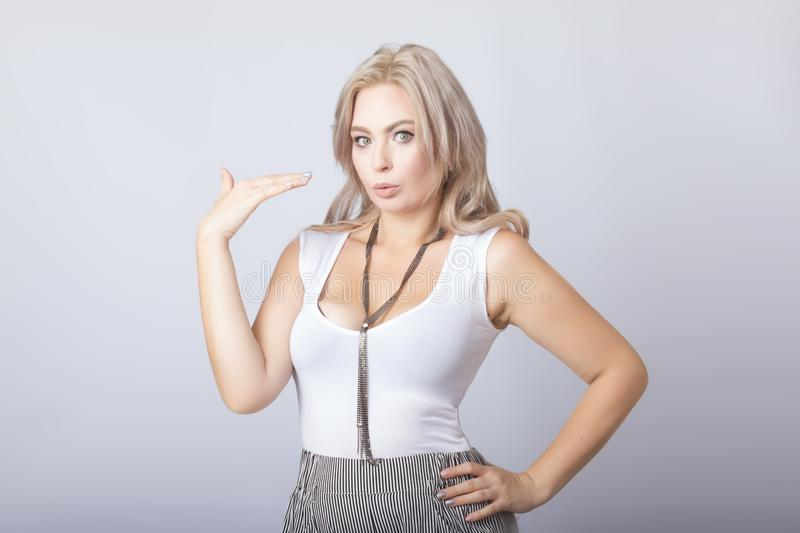 Portrait of smiling blonde woman standing over grey background stock image