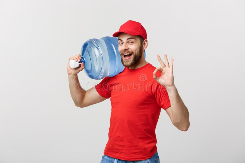 Portrait smiling bottled water delivery courier in red t-shirt and cap carrying tank of fresh drink and showing ok. Isolated over white background royalty free stock photo