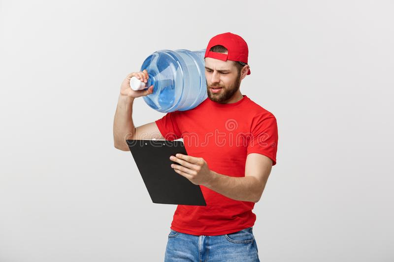 Portrait smiling bottled water delivery courier in red t-shirt and cap carrying tank of fresh drink and showing thumb up royalty free stock photo