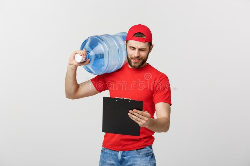 Portrait smiling bottled water delivery courier in red t-shirt and cap carrying tank of fresh drink and showing thumb up royalty free stock images