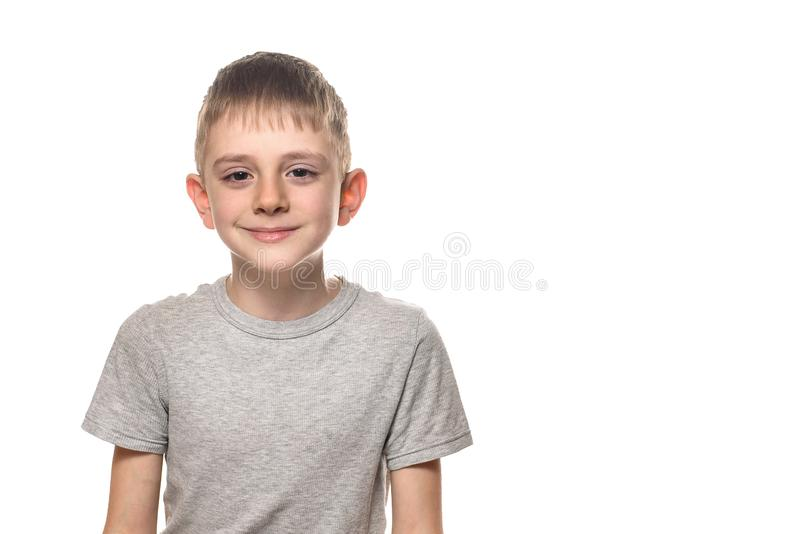 Portrait of a smiling boy in a gray t-shirt. Schoolboy. White background, place for text royalty free stock photography