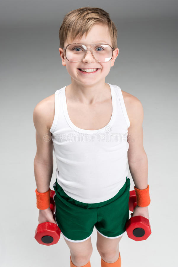 Portrait of smiling boy holding dumbbells royalty free stock image