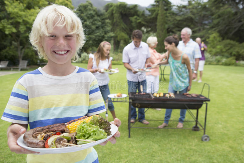 Portrait of smiling boy holding plate of barbecue with family in background stock photos