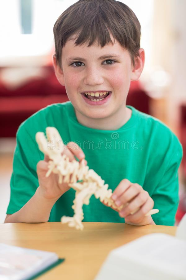 Portrait Of Boy Making Model Dinosaur At Home stock photo
