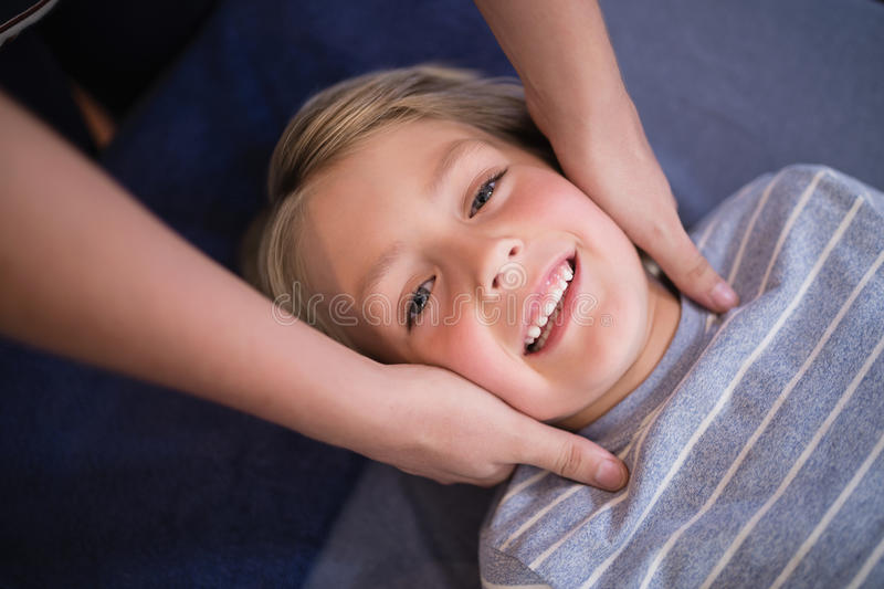 Portrait of smiling boy receiving neck massage from female therapist. At hospital ward stock photos