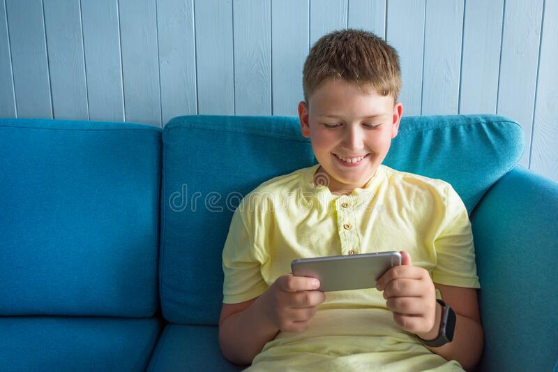 Portrait of a smiling boy with a smartphone in his hands. The child looks into the phone royalty free stock images
