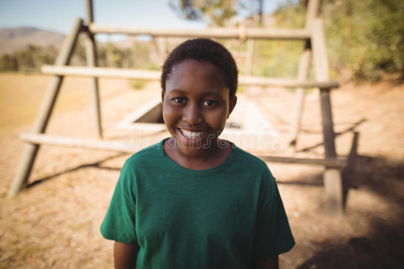 Portrait of smiling boy standing in boot camp stock photography