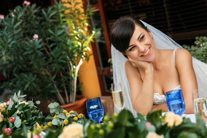 Portrait of a smiling bride at the wedding table stock images