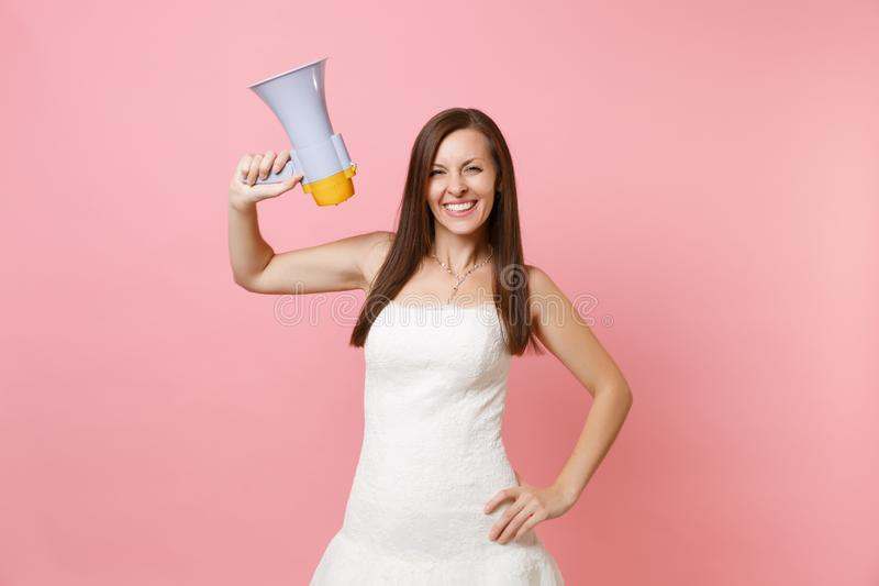 Portrait of smiling bride woman in beautiful white lace wedding dress standing and holding megaphone on pink stock photos