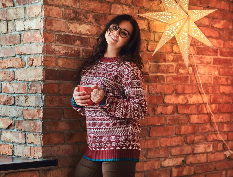 Portrait of a smiling brunette girl wearing eyeglasses and warm sweater holding a cup of coffee while leaning on a brick royalty free stock photography