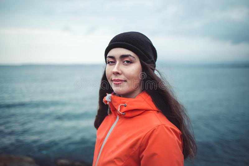 Portrait of a smiling brunette woman with long hair, wearing a hat and an orange jacket. In the background the sea and the horizon royalty free stock photo