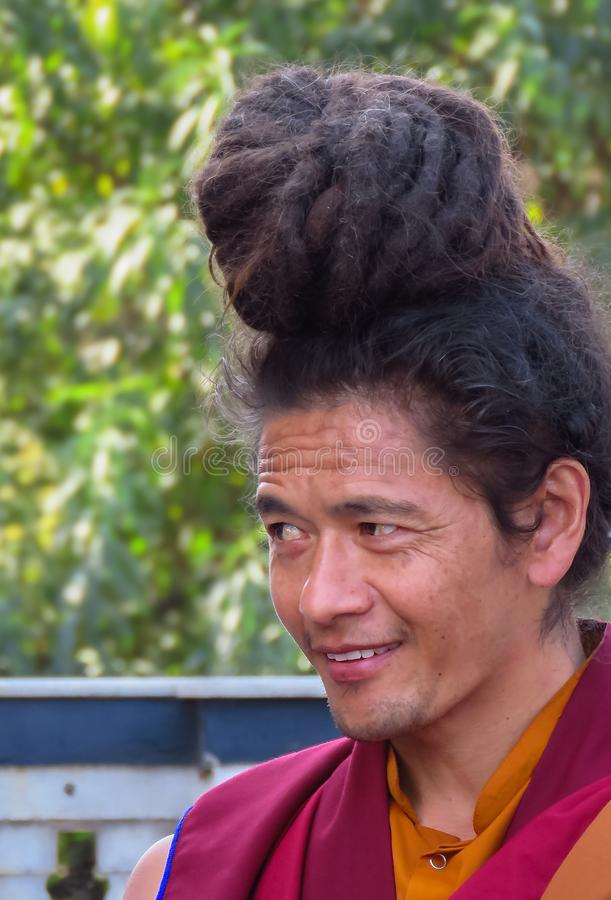 Portrait of a smiling buddhist monk, Kathmandu, Nepal. Close up of a buddhist monk wearing his long hair in a bun on his head, Kathmandu, Nepal stock images