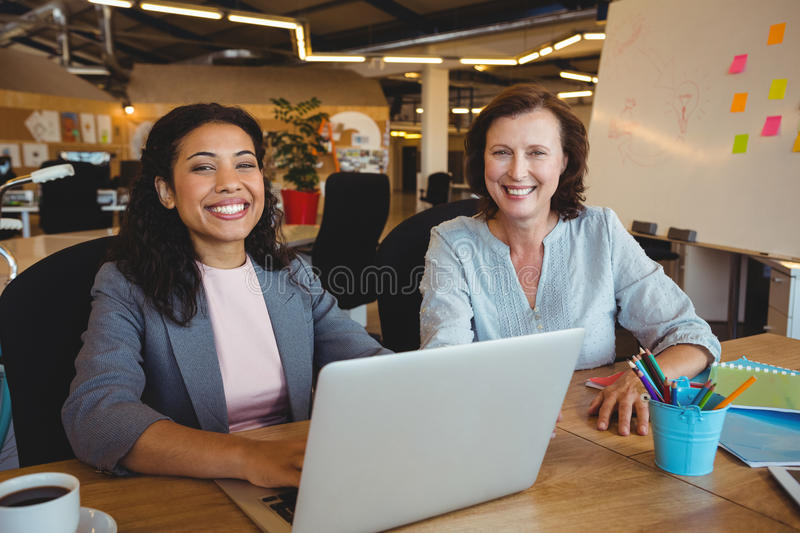Portrait of smiling business executives sitting at desk royalty free stock photography