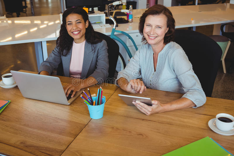 Portrait of smiling business executives using laptop and digital tablet stock photos