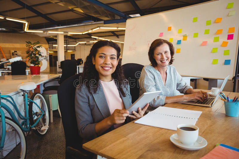 Portrait of smiling business executives using laptop and digital tablet stock image