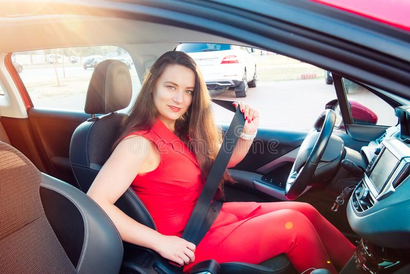 Portrait of smiling business lady, caucasian young woman driver in red summer suit looking at camera and putting on her seat belt royalty free stock image