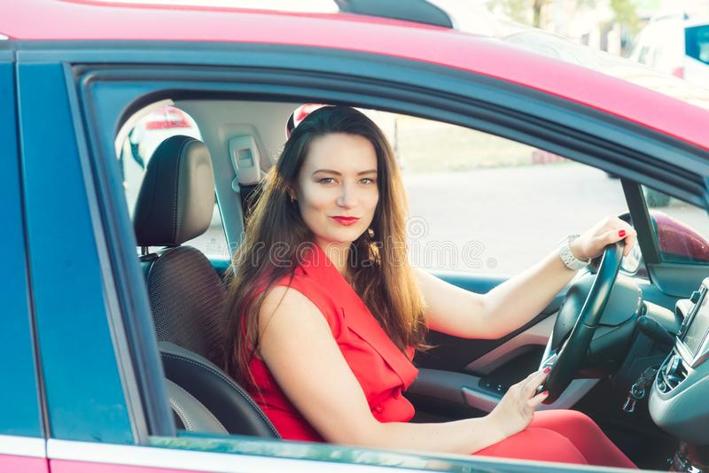 Portrait of smiling business lady, caucasian young woman driver in red summer suit looking at camera and smiling while sitting stock images
