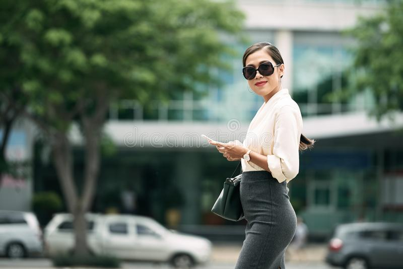 Pretty business lady. Portrait of smiling business lady in sunglasses with phone royalty free stock photography