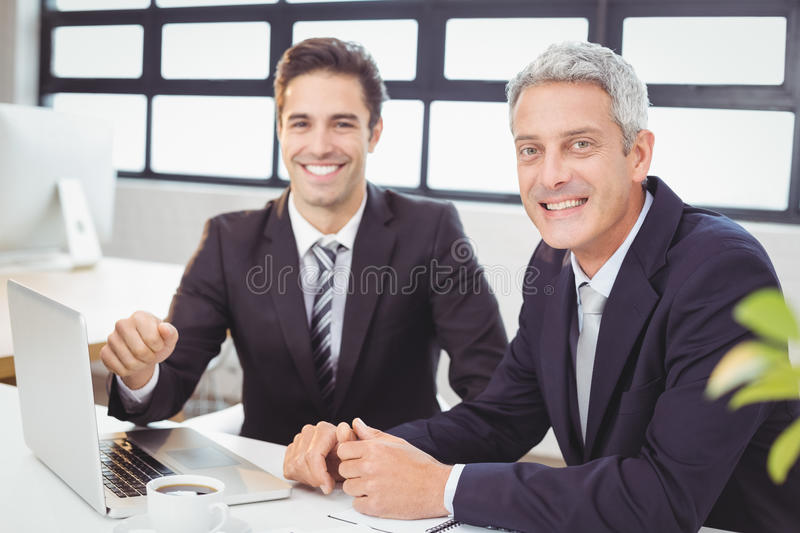 Portrait of smiling business people with laptop stock photography