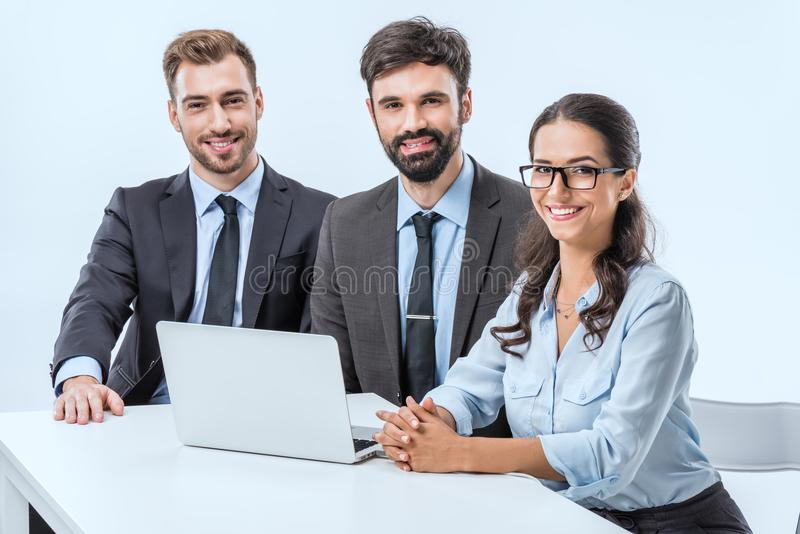 portrait of smiling business people looking at camera while sitting at workplace stock photos