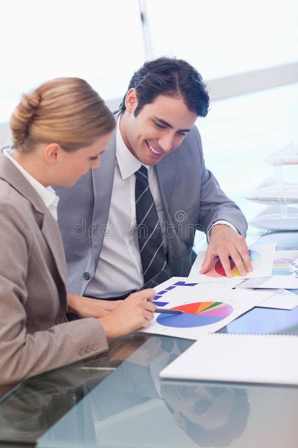 Portrait of smiling business people studying statistics. In a meeting room stock image