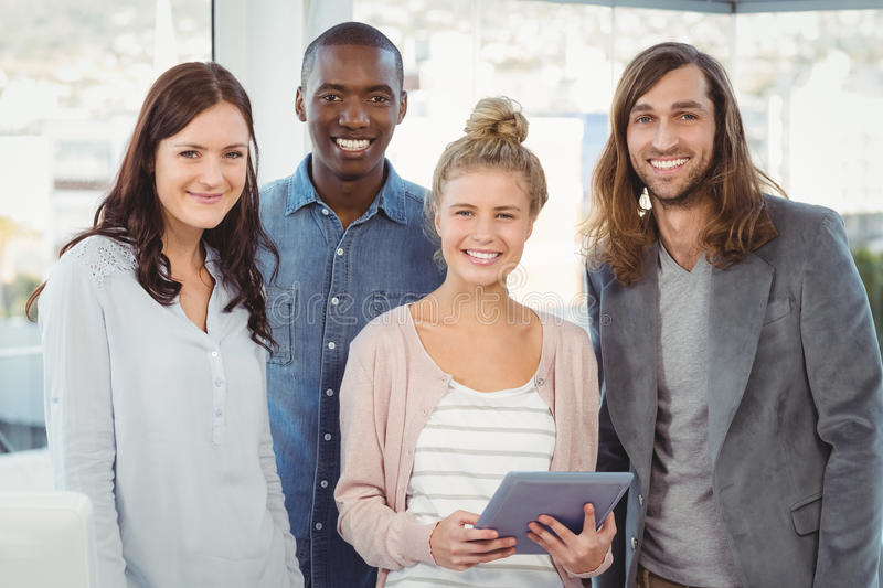 Portrait of smiling business team with woman holding digital tablet. Portrait of smiling business team with women holding digital tablet at office stock images