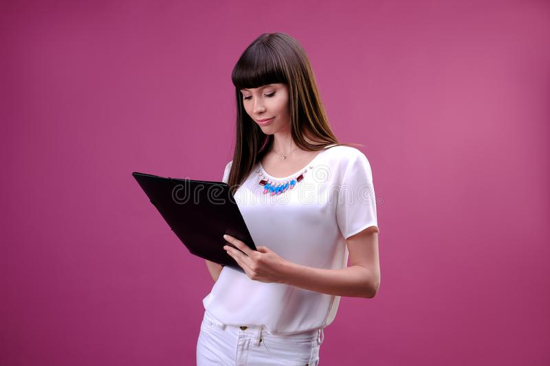 Portrait of smiling business woman with pen and paper folder. Young pretty worker writing something in her papers stock images