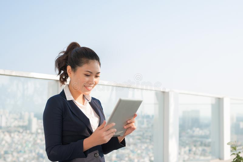 Portrait of smiling business woman using tablet pc stock image