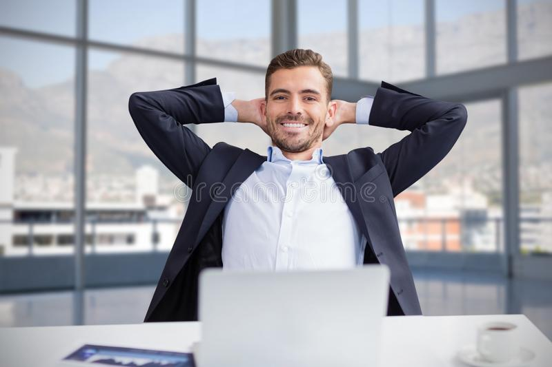 Composite image of portrait of smiling businessman with hands behind head sitting against white back stock photography