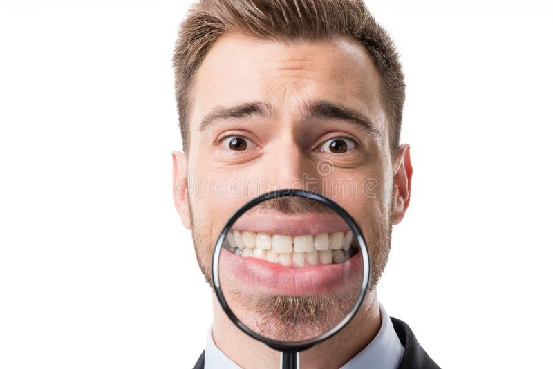 portrait of smiling businessman holding magnifying glass near teeth stock photography