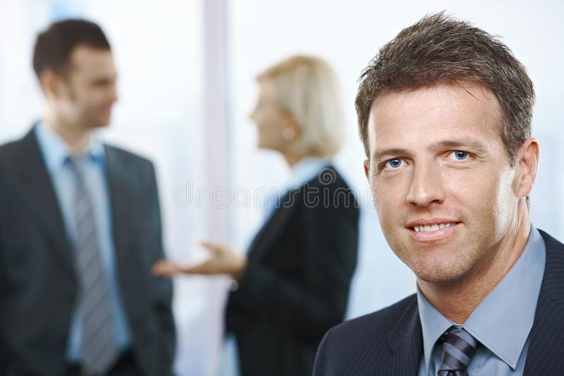 Portrait of smiling businessman. Looking confident with coworkers in background royalty free stock photo